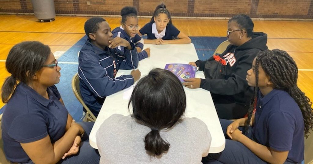 Group sits at table in gymnasium during Family Math Night