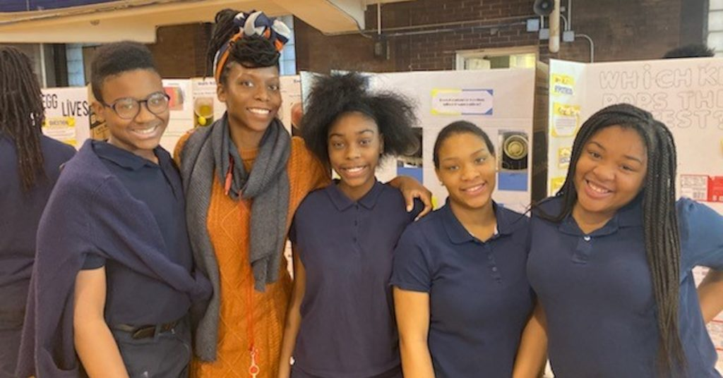 Group poses for photo in front of 2019 Science Fair project