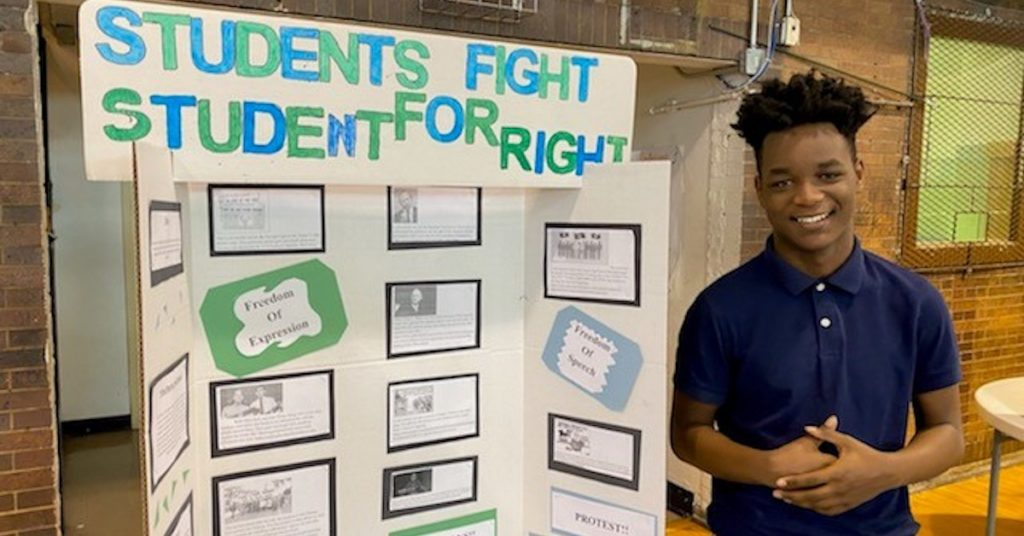Alain Locke student stands in front of his submission to the 2020 History Fair