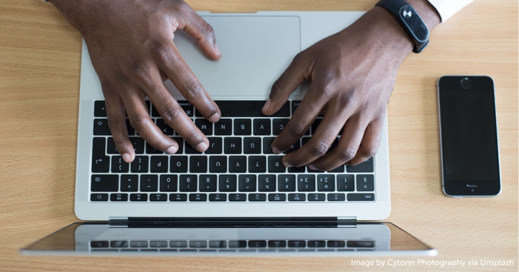 Close-up of man's hands typing on laptop computer.
