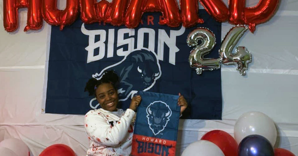 Alain Locke alumnus Armaní Washington poses before Howard Bison flag